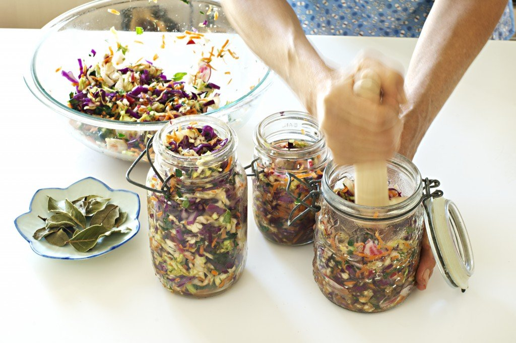 Pressing the sliced and brined vegetables into jars for Rainbow Sauerkraut